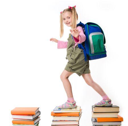backpack school: Portrait of girl with backpack walking from top to top of book piles