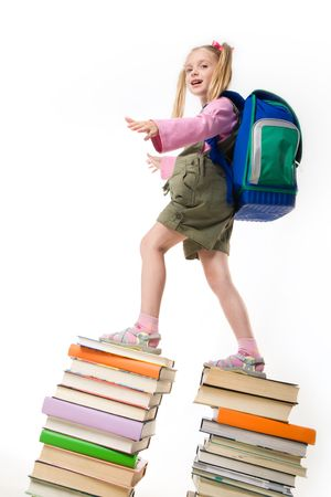 Portrait of beautiful schoolgirl standing on the top of books  photo