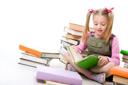 Portrait of pretty schoolgirl reading textbook near pile of books  Stock Photo - 3382696