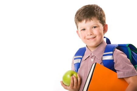 Portrait of cute schoolboy holding green apple and book looking at camera over white background photo