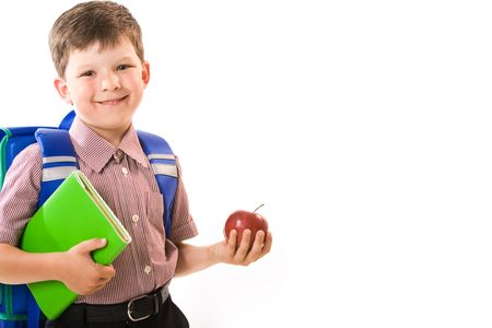 boy alone: Portrait of happy pupil with apple and book in hands looking at camera with smile isolated on white background Stock Photo
