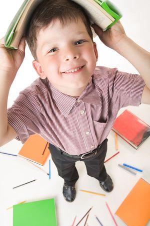 diligente: Fisheye foto de muchacho diligente con su libro sobre la cabeza, mientras que hacer la tarea
