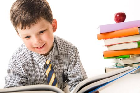 diligent: Photo of diligent schoolchild reading book with stack of textbooks near by Stock Photo