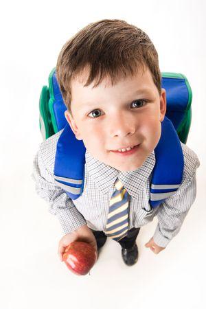 ni�os contentos: Vista desde arriba del cute mochila escolar con manzana y mirando la c�mara Foto de archivo