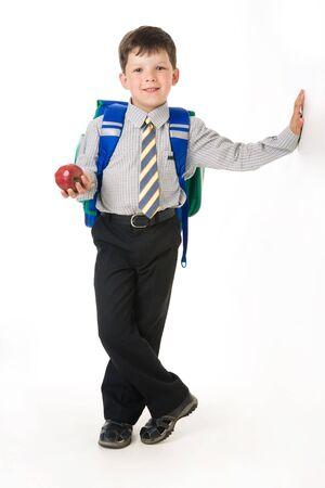 diligente: Retrato de ni�o diligente con manzana y mochila de pie en el estudio Foto de archivo