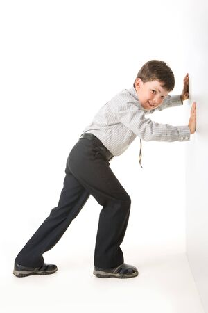 Photo of schoolboy standing near white wall and setting against it
