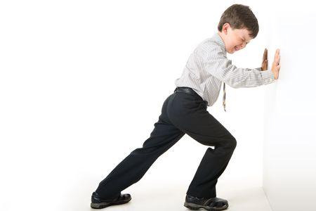 pushing: Afbeelding van schooljongen waardoor grote inspanning tijdens het instellen tegen de muur Stockfoto