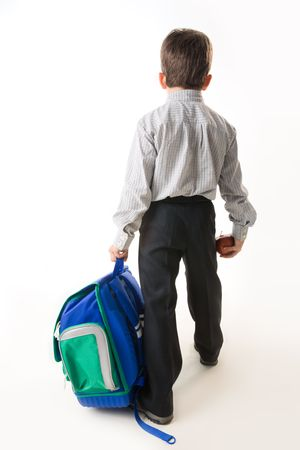 Back of schoolboy holding backpack and apple while going to school Stock Photo