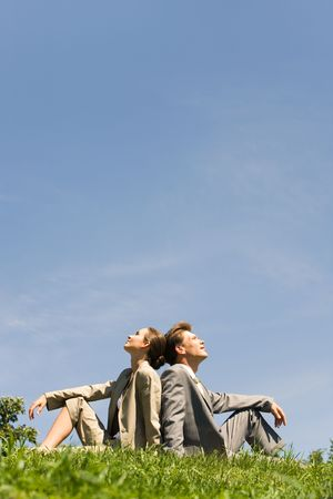 blue sky thinking: Image of two businesspeople sitting a back to each other on the lawn