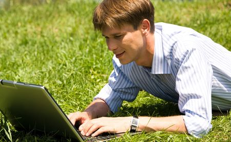 Portrait of handsome manger typing on the laptop outdoor photo