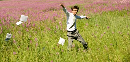 Photo of happy businessman running upon green field on windy day in summer photo
