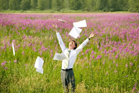 Photo of glad young man standing on green field with his arms raised and some business papers over his head photo