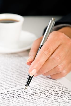 hand holding pen: Close-up of female�s hand holding pen over business document with cup of coffee near by
