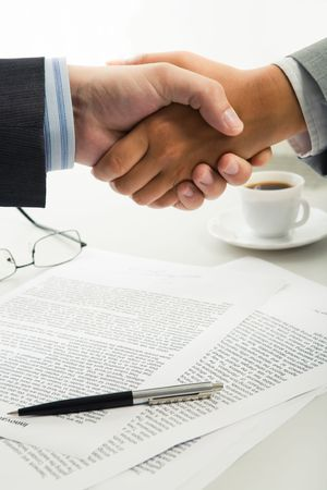 teamwork hands: Image of business handshake over table with documents, pen, glasses, cup on it Stock Photo