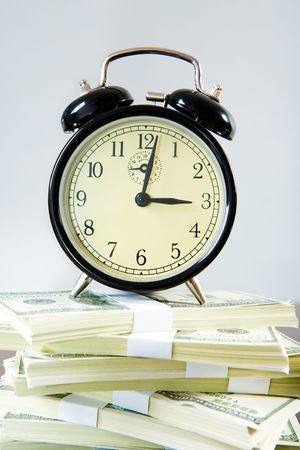 hoard: Photo of alarmclock standing on stack of dollars over grey background