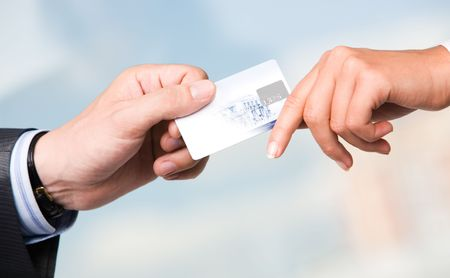 Close-up of transfer of credit card from maleÂ's hand to that of female over blue background