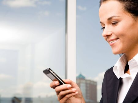 Image of pretty woman holding her mobile and sending sms   photo