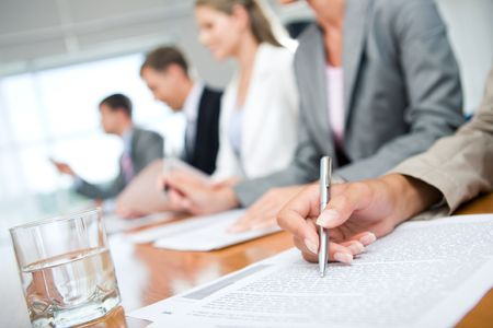 Close-up of woman's hand with pen over document on background of business group photo