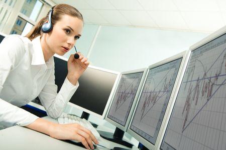 audifonos: Foto de graves representante de servicio al cliente antes de la sesi�n ordenador mientras consulta a alguien en la oficina