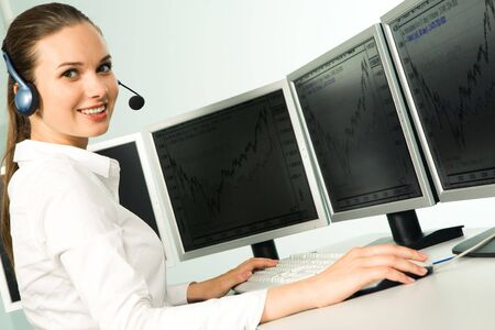 Portrait of beautiful telephone operator sitting at the table with several computers on it