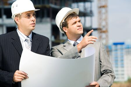 Portrait of successful workers holding a project and discussing a building place Stock Photo - 3387432