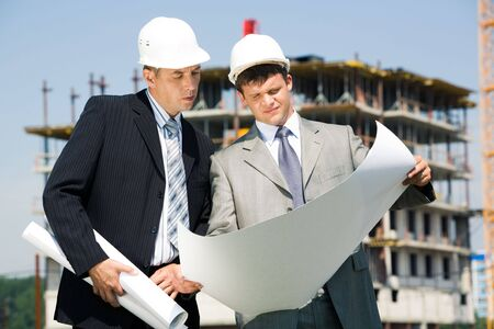 construction project: Image of architect and worker looking at architectural project