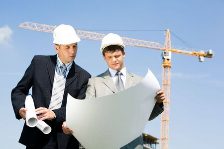 Portrait of two confident foreman looking at project on the background of sky and crane Stock Photo - 3387255