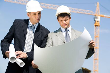 Portrait of two businesspeople with helmets on their heads looking at document outside  photo