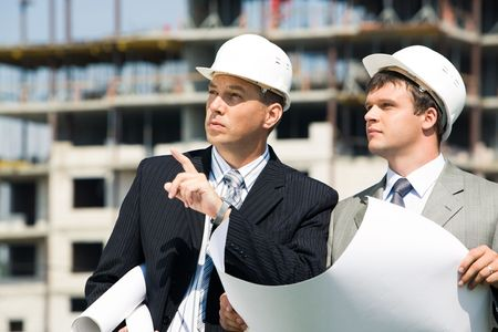 Portrait of successful boss explaining and pointing to a place to foreman   photo