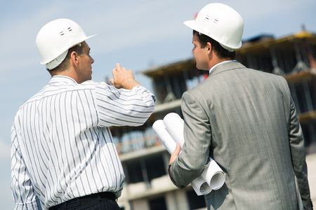 Image of confident workers standing a back and discussing a building place  photo