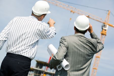 Image of two workers standing a back and showing at crane  photo