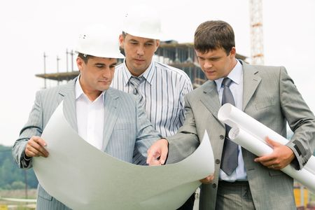 Image of three businessmen looking at architectural project at meeting   photo
