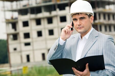 Portrait of serious architect calling on the telephone on the background of building  photo