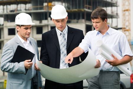 communication industry: Portrait of three builders standing at building site and discussing new project held by one of men