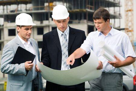 edificio industrial: Retrato de tres constructores de pie a obras de construcci�n y discusi�n de nuevos proyectos en manos de uno de los hombres