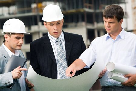workgroup: Portrait of workgroup of builders looking at new project in boss� hands while one of men pointing at something