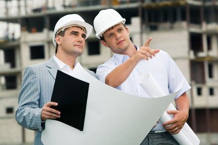 building contractor: Photo of young engineer showing something to his colleague during meeting at building site Stock Photo