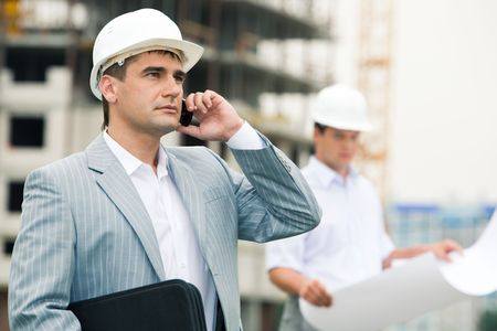 executive helmet: Photo of confident foreman speaking on the cellular phone on the background of employee