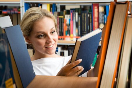 Image of smart student holding book in hands and looking at it with smile in library photo