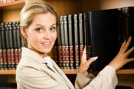 Portrait of business lady touching books that stand on shelf and looking at camera photo