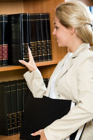 Profile of confident woman standing by the bookshelf and choosing books photo