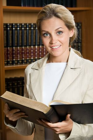 tomes: Portrait of elegant woman holding open book and looking at camera on background of shelves with tomes