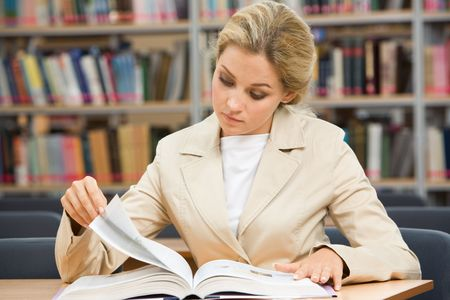 Portrait of serious female leaning over book in the library and reading it photo