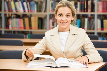 encyclopedias: Retrato de feliz estudiante sentado en la biblioteca de libros de texto antes y mirando la c�mara