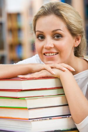 Portrait of pretty student putting her chin on hand over pile of books photo