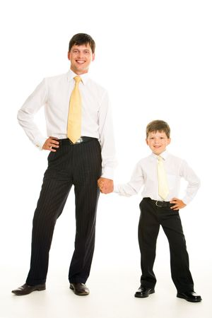 Portrait of smiling man and his son holding by hands over white background