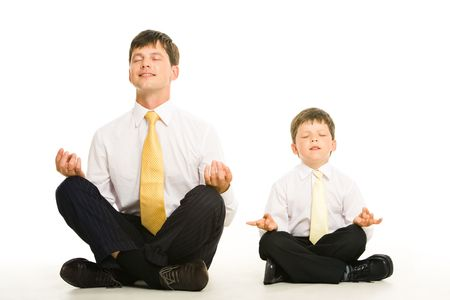 Photo of father and son sitting in pose of lotus with their eyes closed and meditating photo
