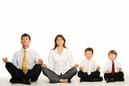 Photo of friendly family sitting in pose of lotus in a row and meditating over white background photo