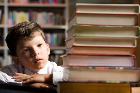 diligente: Cara de ni�o diligente buscando a pila de libros en la biblioteca