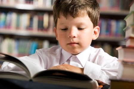 Close-up of cute boy reading book while preparing for lesson in library Stock Photo